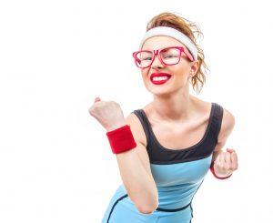 Photographie d'une jeune femme blonde en tenue d'entraînement dans une attitude loufoque. Représentation de l'entraînement physique.