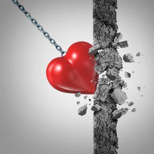 Photographie d'une boule de démolition en forme de coeur qui fracasse une structure rectangulaire en béton. Représentation de la destruction de la Saint-Valentin et des clichés liés l'amour.