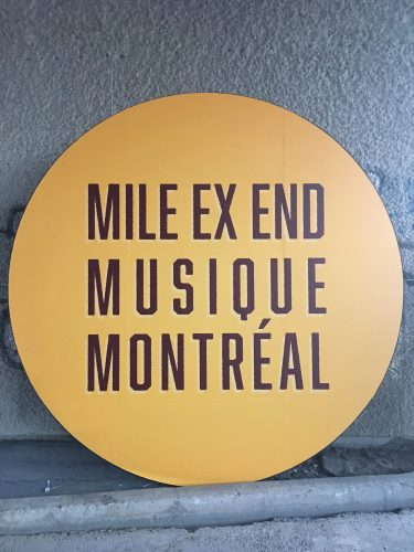Panneau en forme de disque jaune-orangé avec lettrage aux armes du Mile Ex End Musique Montréal. Panneau décorant l'un des piliers du viaduc Van Horne, à l'entrée du site.