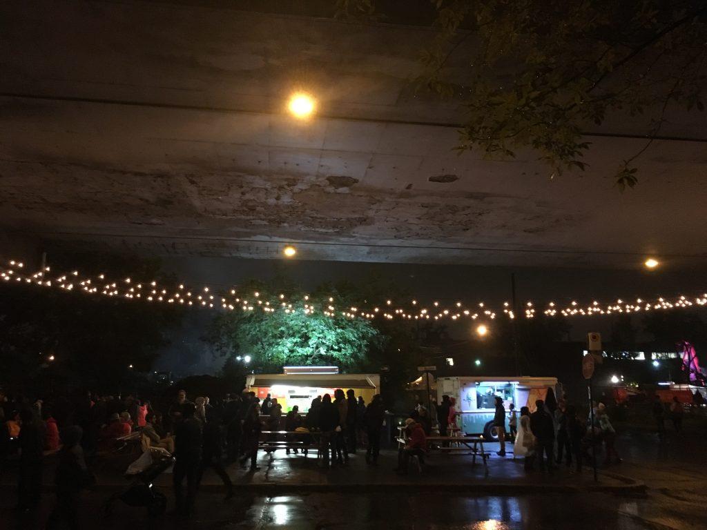 Des festivaliers réfugiés sous le viaduc Van Horne à la nuit tombée. À l'arrière-plan, paysage de cantines mobiles et de festivaliers marchant sous la pluie au Mile Ex End Musique Montréal (dimanche 3 septembre 2017).