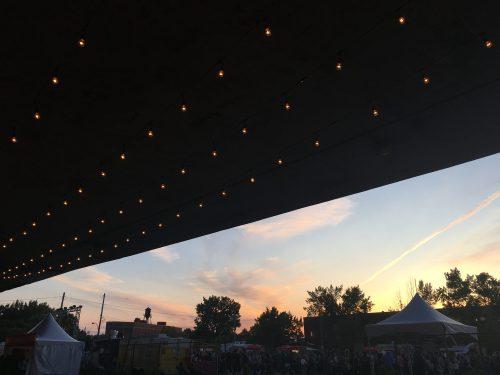 Gros plan sur les lumières décoratives installées sous le viaduc. À l'arrière-plan, côté droit, on peut apercevoir le coucher du soleil et la foule présente sur le site de la scène Mile Ex End du Mile Ex End Musique Montréal.