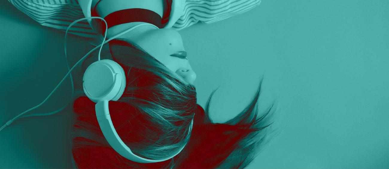 Femme portant des écouteurs, le visage recouvert par sa chevelure.