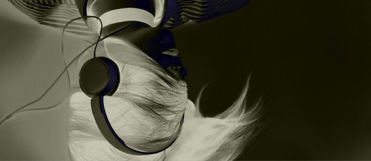 Femme portant des écouteurs, le visage recouvert par sa chevelure. Inversion chromatique.
