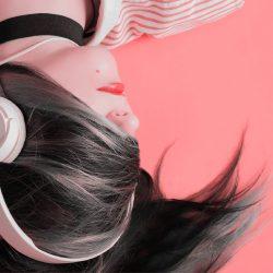Femme au visage recouvert par sa chevelure, portant des écouteurs.